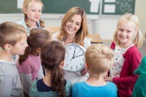 Lehrerin erklärt Schülern die Uhr