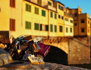Liebesschlösser im Abendlicht mit der Ponte Vecchio im Hintergrund
