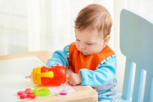 kleiner Junge spielt mit Tasse
